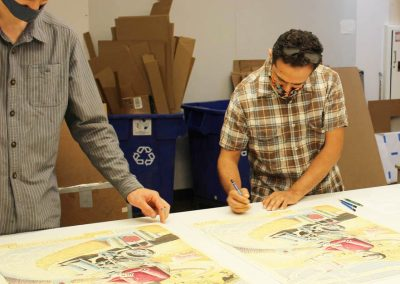 Tipping Points artist Eric Garcia signing prints with Tamarind Curator Ben Schoenburg