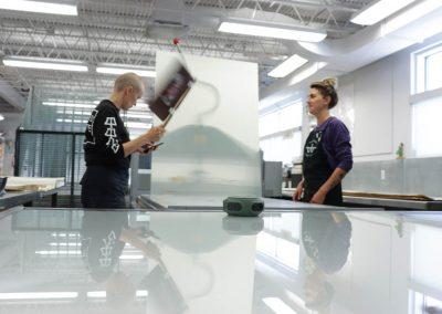 Tamarind Apprentice Printer Alyssa Ebinger and Tamarind Master Printer and Workshop Manager Valpuri Remling fanning a plate on the press