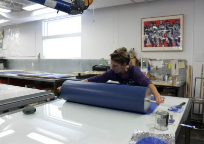 Tamarind Apprentice Printer Alyssa Ebinger rolling blue ink onto a roller