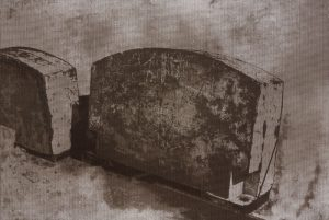 Two-color lithograph by Harold Mendez. Two mottled gravestones in gray and black sit at an angle from lower right to the left center edge.